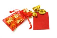 Lingotes e moedas do ouro no saquinho vermelho e no pacote vermelho Imagem de Stock