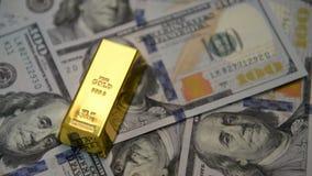 Lingotes y dólares del oro en una tabla metrajes