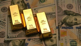 Lingotes y dólares del oro en una tabla con brillante al efecto oscuro almacen de video