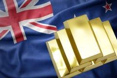 Lingots d'or brillants sur le drapeau de la Nouvelle Zélande Photos stock