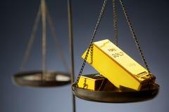 Lingots d'or sur l'échelle en laiton Photographie stock libre de droits
