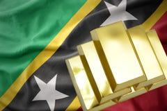 Lingotti dorati brillanti sul san San Cristobal e sulla bandiera del Nevis Fotografia Stock Libera da Diritti