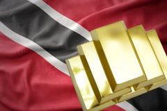 Lingotti dorati brillanti sulla bandiera dei Trinità e Tobago Fotografia Stock Libera da Diritti
