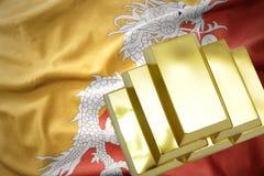 Lingotti dorati brillanti sulla bandiera del Bhutan Immagini Stock Libere da Diritti