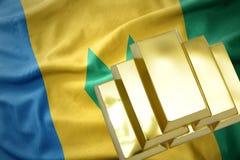 Lingotti dorati brillanti sulla bandiera del Saint Vincent e Grenadine Immagine Stock