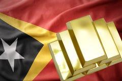 Lingotti dorati brillanti sulla bandiera del Timor Est Immagine Stock