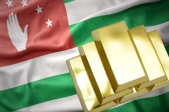 Lingotti dorati brillanti sulla bandiera dell'Abkhazia Immagine Stock