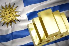 Lingotti dorati brillanti sulla bandiera dell'Uruguai Fotografia Stock Libera da Diritti