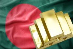 Lingotti dorati brillanti sulla bandiera della Bangladesh Fotografia Stock
