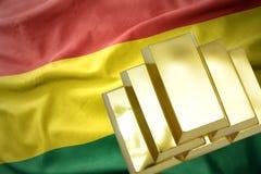 Lingotti dorati brillanti sulla bandiera della Bolivia Fotografie Stock