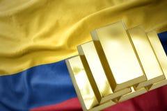 Lingotti dorati brillanti sulla bandiera della Colombia Fotografie Stock