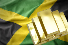 Lingotti dorati brillanti sulla bandiera della Giamaica Fotografie Stock