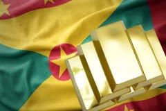 Lingotti dorati brillanti sulla bandiera della Granada Fotografia Stock