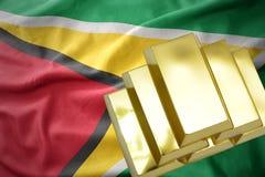 Lingotti dorati brillanti sulla bandiera della Guyana Fotografia Stock