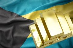 Lingotti dorati brillanti sulla bandiera delle Bahamas Immagini Stock Libere da Diritti