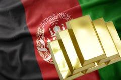 Lingotti dorati brillanti sulla bandiera di Afghanistan Fotografia Stock