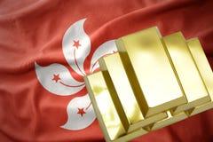 Lingotti dorati brillanti sulla bandiera di Hong Kong Fotografia Stock Libera da Diritti