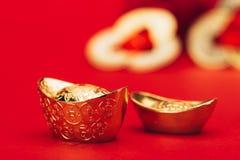 Lingotti dorati cinesi sulla superficie di rosso Fotografia Stock Libera da Diritti