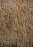 Lingua antica intagliata in pietra Fotografia Stock