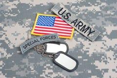 Linguetta delle forze speciali dell'ESERCITO AMERICANO con le medagliette per cani in bianco sull'uniforme del cammuffamento Fotografia Stock