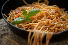 Linguine with Basil and Red Sauce in Cast Iron Pan Stock Photo