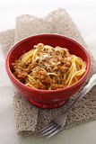 Linguine Bolognese. Linguine pasta tossed with Bolognese sauce in a red clay bowl Stock Image
