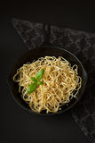 Linguine in a Cast Iron Pan with Basil on Black Background royalty free stock image