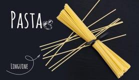 Linguine italien cru de pâtes sur le fond noir de pierre d'ardoise Image libre de droits