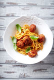 Linguine with meatballs, tomato sauce and basil leaves Royalty Free Stock Image