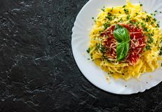 Linguine pasta with fresh tomato sauce, grated cheese and basil. In white plate on black background. with copy space. top view Royalty Free Stock Photos