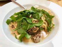 Linguini Pasta with Lamb Meat, Cream Sauce and Arugula, Rocket or Rucola Leaves. stock photo
