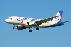 A linha aérea dos aviões A319-112 VP-BTE Ural Airlines voa afastado no céu azul sem nuvens Fotos de Stock Royalty Free
