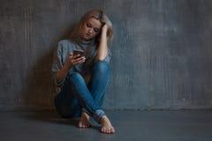 Linha aberta, auxílio psicológico Jovem mulher de sofrimento que senta-se em um canto com um telefone em sua mão fotografia de stock royalty free