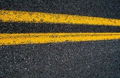 Linha amarela dobro em uma estrada asfaltada Fotografia de Stock