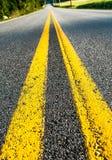 Linha amarela dobro em uma estrada asfaltada que desvanece-se na distância Fotografia de Stock Royalty Free