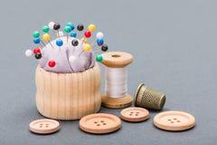 Linha, botões, dedal e almofada de alfinetes Fotografia de Stock Royalty Free