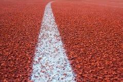 Linha branca em uma superfície do fundo da pista de atletismo, de raso Imagens de Stock Royalty Free