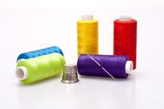 Linha colorida para sewing com agulha e dedal Foto de Stock Royalty Free