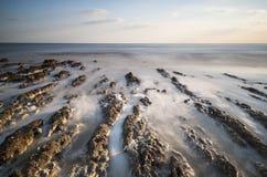 Linha costeira rochosa da paisagem longa da exposição no por do sol Fotos de Stock