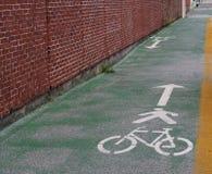 Linha da bicicleta ao lado de uma parede de tijolo Fotos de Stock