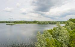 Linha de alta tensão sobre a costa de um lago na mola fotografia de stock