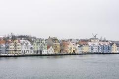 Linha de casas coloridas ao lado da água com um moinho de vento em um fundo Foto de Stock