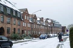 Linha de casas com um quintal e muita neve no telhado e nos carros e no fundo do roadthe Foto de Stock Royalty Free