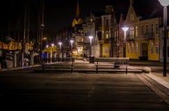 A linha de casas durante a noite iluminou-se pela luz de rua antes da parte dianteira da água do inverno e pelo porto com navios Fotos de Stock