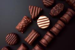 Linha de chocolates de formas diferentes em um fundo preto foto de stock