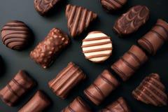 Linha de chocolates de formas diferentes em um fundo preto fotos de stock