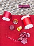 Linha de costura, botões, dedal no pano vermelho Fotografia de Stock