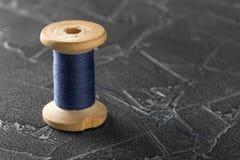 Linha de costura em um carretel de madeira velho com fundo concreto escuro fotos de stock royalty free