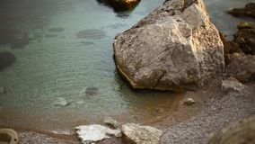 Linha de mar rochosa calma bonita e praia rochosa pequena entre penhascos barco inflável vazio na praia vídeos de arquivo