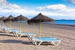 Linha de parasóis na praia espanhola da areia Fotografia de Stock Royalty Free
